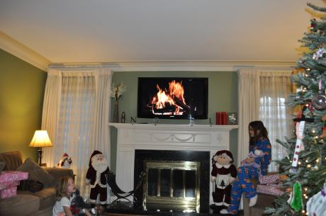 Our living room at our G.P. home, with Christmas tree and a warming fire burning on the TV