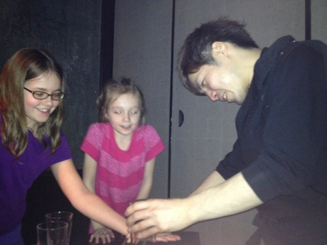 "The girls watch a ""Ninja"" perform magic and sleight-of-hand tricks."