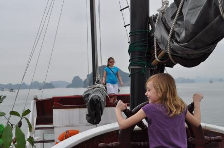 Stephanie steering our Chinese Junk in Halong Bay as Cassidy looks on warily.