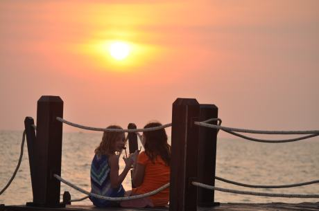 The girls chat as the sun sets over the Sea of Thailand.