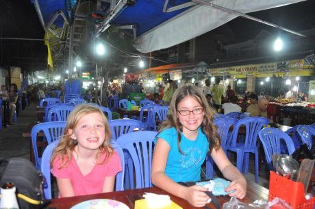 The girls settle in for something to eat and drink at the night market in Duong Dong.