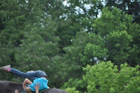 Stephanie doing a backward summersault on a moving horse.