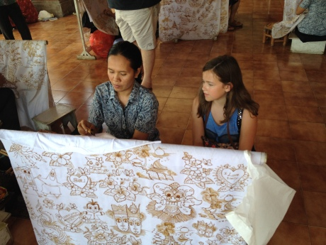 Cassidy watching a women apply a Batik design to her shirt.