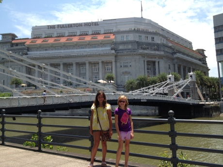 The girls in front of the Fullerton Hotel in Singapore.