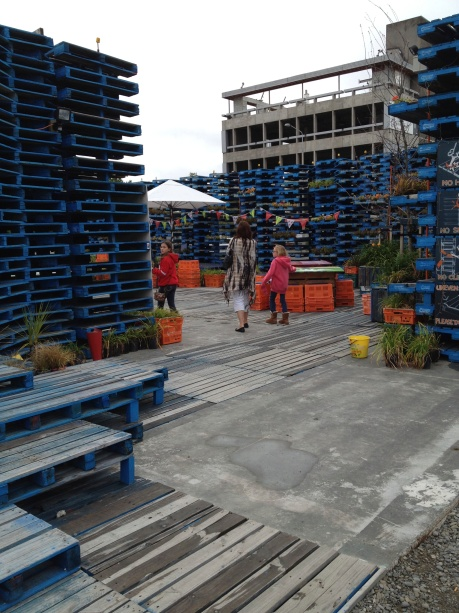 "Karen and the girls entering the ""Gap-filler pallet pavilion"", and outdoor bar and restaurant built after the 2011 Christchurch earthquake"