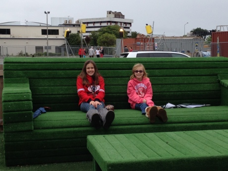 Girls on oversized outdoor furniture as part of Christchurch Gap Filler project.  Dance-o-mat in the background.