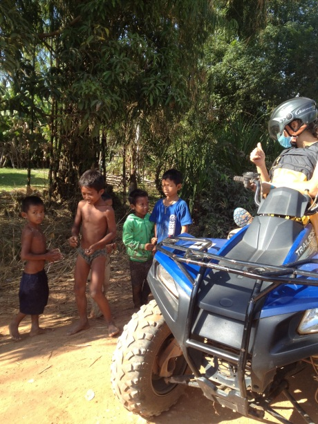 My friend Teresa and family meeting locals in the Cambodian countryside while riding ATV's.