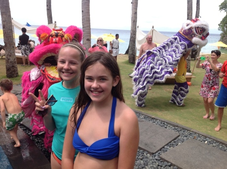 Cassidy and her friend Henriette as procession of beasts for Chinese New Year stalks behind them.