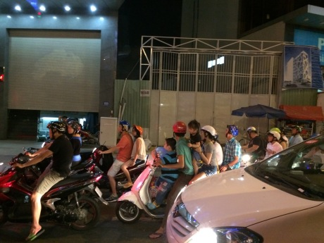 Scooter madness in Saigon. Note family of 4 in foreground -- helmets only required for adults?!?!