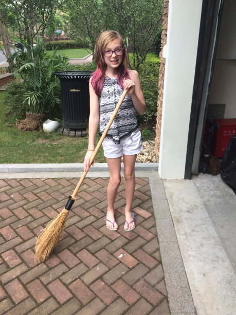 Steph with one of those crazy, straw taped to a stick brooms.